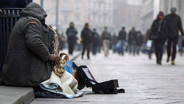 A beggar plays a saxophone in downtown Milan earlier this month. Italian bond yields reached new euro-era highs at an auction Friday.