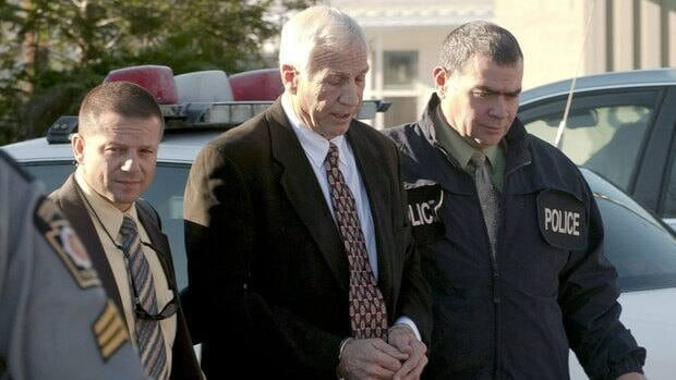 Former Penn State football defensive coordinator Jerry Sandusky, centre, is escorted in handcuffs to a waiting police car in Bellefonte, Pa.