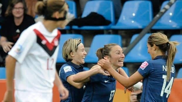 France's Gaetane Thiney, second from right, is congratulated by her teammates after scoring the first of her two goals during the opening half against Canada and star forward Christine Sinclair (12).
