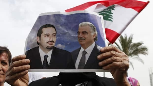 A Lebanese woman supporter of outgoing prime minister Saad al-Hariri holds a photograph of him and his father, former prime minister Rafik al-Hariri, at the site of the latter's assassination in Beirut, in March. Saad al-Hariri was toppled in January  by Hezbollah and its allies.