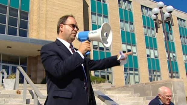 Liberal Leader Kevin Aylward speaks to public pensioners in front of Confederation Building.