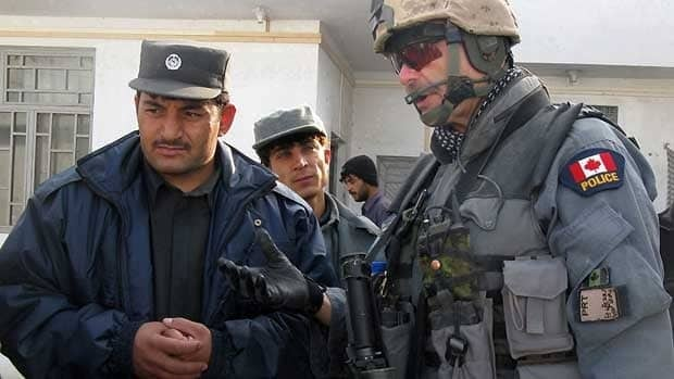 Canadian Staff Sgt. Higgins Elliott, right, checks in with Afghan National Police commander Wali Jan Sarhadi at a police substation in Kandahar City in 2008. (Tobi Cohen/Canadian Press)