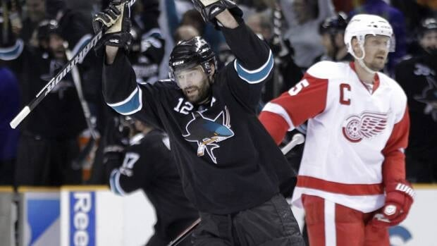 San Jose's Patrick Marleau, left, celebrates as Detroit captain Nicklas Lidstrom skates past at the end of Game 7.