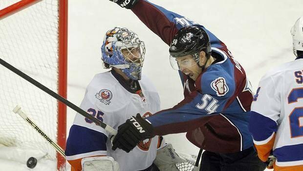 Avalanche's David Jones (54) celebrates Kyle Quincey's game-winning goal past Islanders goalie Al Montoya in overtime.