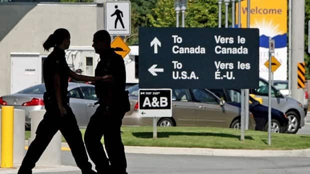 Canadian border guards are silhouetted as they replace each other at an inspection booth at the Douglas border crossing on the Canada-U.S. border in Surrey, B.C., in 2009. Border guards at crossings in B.C. seized 10 loaded handguns and a shotgun last week.