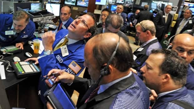 Traders work on the floor of the New York Stock Exchange at the opening bell Monday.