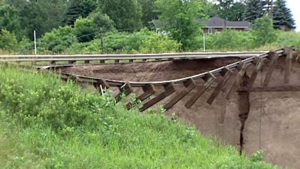 Guard rails on Highway 148 hang over a chasm after overflowing waters washed out the road.