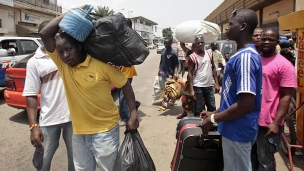 Residents walk with their belongings towards a railway station as they leave Abidjan, Ivory Coast. Rebel forces backing Ivory Coast's internationally recognized president seized the capital of Yamoussoukro Wednesday.