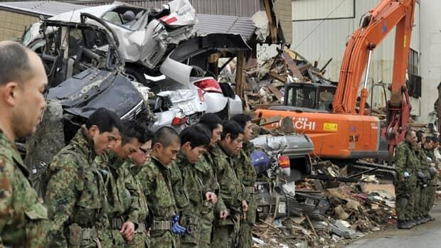 Self-Defence Forces members offer a prayer for the dead in Kesennuma, Miyagi prefecture, on Monday. Japan fell silent at 2:46 p.m. to mark one month since a the earthquake hit, spawning a devastating tsunami.