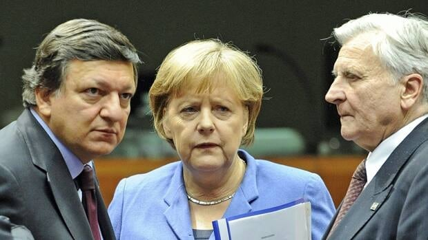 German Chancellor Angela Merkel, speaks with, European Commission President Jose Manuel Barroso, left, and ECB President Jean-Claude Trichet at an EU summit in Brussels on Sunday.