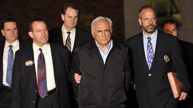 International Monetary Fund managing director Dominique Strauss-Kahn leaves a New York Police Department building on Sunday. A judge ruled Monday that Strauss-Kahn must remain jailed until his next court hearing on attempted rape and other charges.