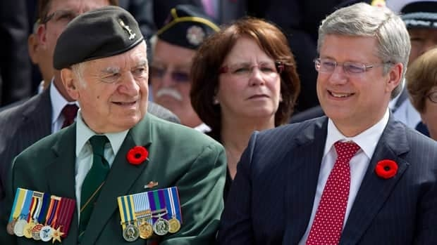 The family members of this Korean war veteran, shown at a wreath-laying ceremony with Prime Minister Stephen Harper in July 2011, could be charged with a criminal offence if they were to wear his military medals.