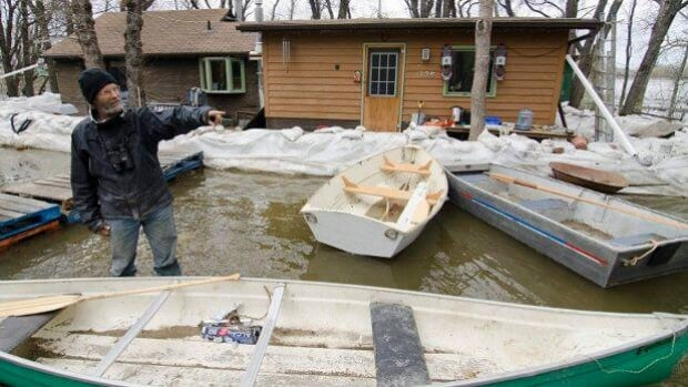 Dave Barnes talks with a reporter as the swollen Assiniboine River threatens his home near Brandon, Man., on Wednesday.
