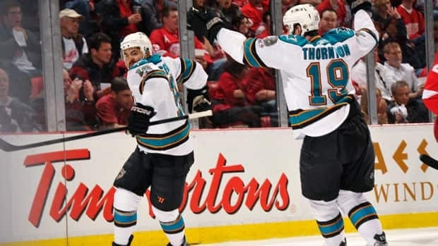 Devin Setoguchi, left, of the San Jose Sharks celebrates his first period power play goal with teammate Joe Thornton.
