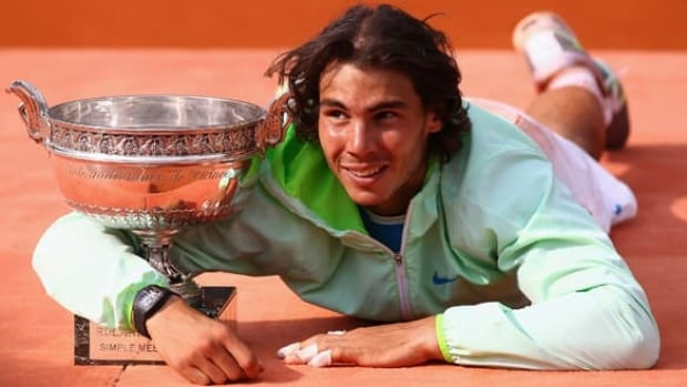 Rafael Nadal of Spain poses for photographers on the red clay of Roland Garros upon winning the French Open last June 6.