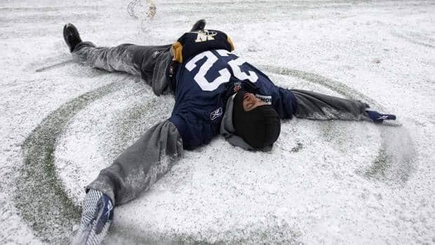 Winnipeg defensive back Darrell Pasco makes a snow angel on the sidelines during Friday practice. The Bombers face Hamilton in the East final on Sunday in weather expected to be cold and windy.