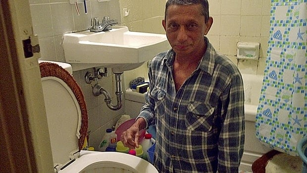 Ramdat Punwassie in his bathroom where he discovered a one-metre long snake coiled up inside his toilet bowl on Tuesday night.