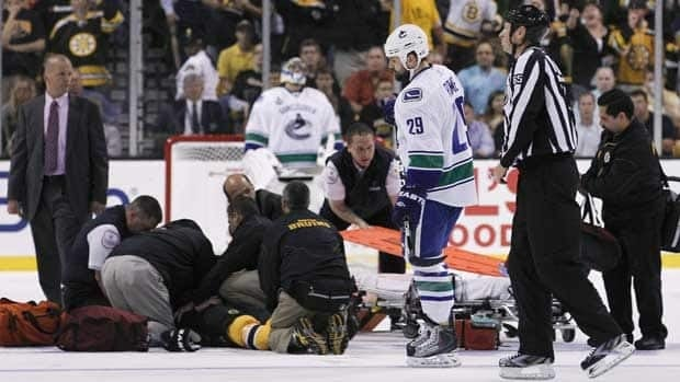 Aaron Rome (29) skates past an injured Nathan Horton after Rome levelled the Bruins forward with a hit in Game 3 of the Stanley Cup final.