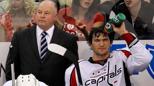 Washington Capitals' Alex Ovechkin cools down on the bench during the 2010 NHL playoffs as coach Bruce Boudreau looks on.