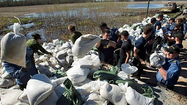 Canadian naval reservists load sandbags to re-enforce a soft spot in the dike along the Assiniboine River. Portage residents are seeking compensation after the government breached a dike earlier this week.