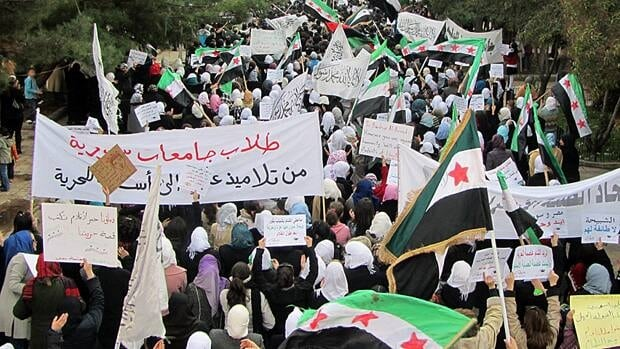 "Demonstrators protesting gainst Syria's President Bashar al-Assad march through the streets in Homs on Tuesday. The banner reads, ""The Syrian Universities students, are students of science, to teachers of freedom.""  REUTERS/Handout"