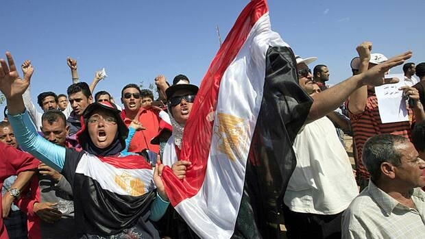 Egyptians carrying their national flag demand former president Hosni Mubarak be tried, as they stand in front of the main hospital of Sharm el-Sheikh, where Mubarak is reported to be inside for treatment, on April 13.