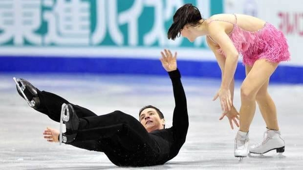 Canada's Scott Moir, left, tumbles while performing his short program with Tessa Virtue on the opening day of the Grand Prix Final in Quebec City.