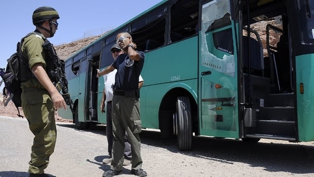 Israeli emergency personnel stand near a bus after it was ambushed north of the Red Sea resort of Eilat on August 18, 2011.