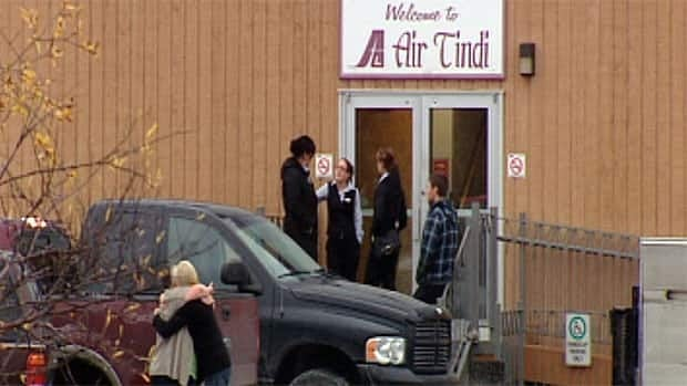 People hug and talk outside the Air Tindi building in Yellowknife after getting news one of the company's planes crashed near Lutselk'e, N.W.T.
