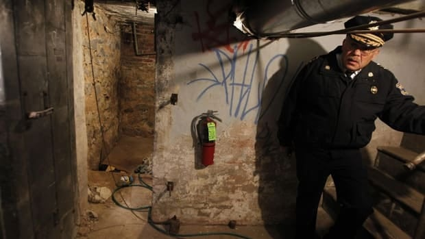 Philadelphia Police Commissioner Charles Ramsey stands by the entrance to the dank basement room in Philadelphia where four weak and malnourished mentally disabled adults, one chained to the boiler, were found locked inside.