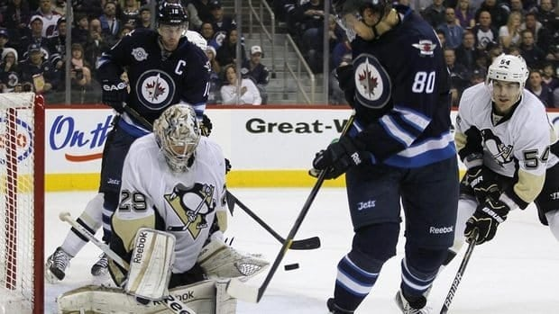 Pittsburgh Penguins goaltender Marc-Andre Fleury, left, makes the save on Winnipeg Jets forward Nik Antropov during the second period of Pittsburgh's win on Friday night.