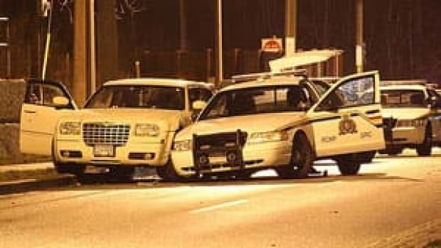 Adam Purdie's Chrysler sits beside a police crusier after the Thursday shooting in Surrey.