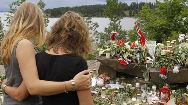 Two young women stand in silence after placing flowers near Sundvollen close to Utoya island, near Oslo, where 68 people were killed.