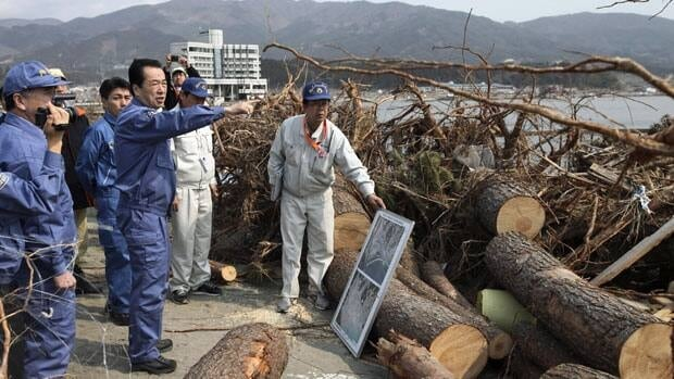 Japanese Prime Minister Naoto Kan, dressed in blue work clothes, points Saturday to some of the destruction in Rikuzentakata, a city in Iwate prefecture that was hit hard by the earthquake and tsunami on March 11.  Associated Press