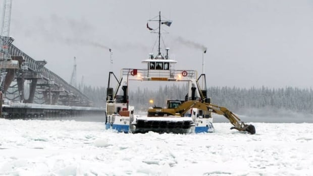 The Merv Hardie ferry uses a backhoe to clear ice from its route across the Mackenzie River in November 2011. The Abraham Francis ferry at Fort McPherson is using a similar technique to keep its channel open longer this season. (N.W.T. Department of Transportation)