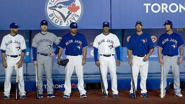 From left, Blue Jays players Jose Bautista, Adam Lind, Ricky Romero, Yunel Escobar, J.P. Arencibia and Brett Lawrie show off the team's new uniforms for 2012.