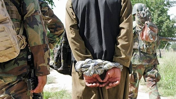 A man Afghan authorities suspect of insurgency-related activities is interrogated during a joint Canadian-Afghan army patrol in the Panjwaii District of Kandahar province in July 2009.