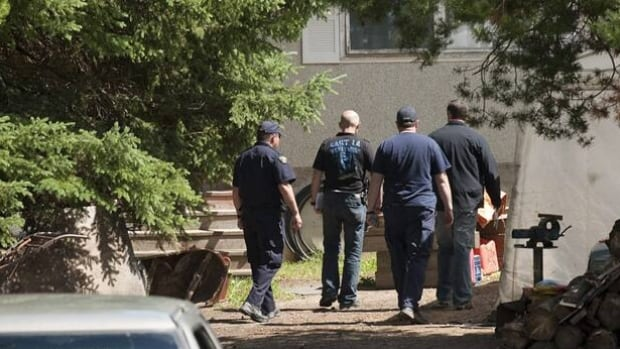 RCMP investigators search a home near MacKay, Alta., on July 20, 2010, where Travis Vader, suspected in the disappearance of Marie and Lyle McCann, was arrested the day before.