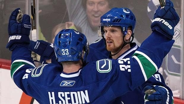 Vancouver Canucks forward Daniel Sedin, right, celebrates his goal in Game 2 with twin brother Henrik.