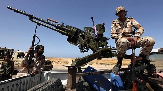 A Libyan rebel mans a vehicle-mounted weapon as they gather in the Al-Noflea area, near Moammar Gadhafi's hometown of Sirte on Monday.
