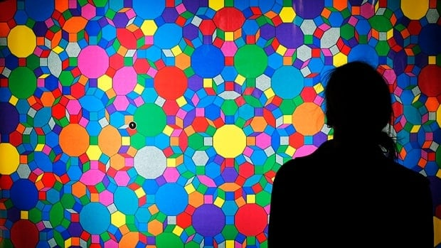 A woman stands in front of an illuminated picture of a quasicrystal on display at the Science Tunnel multimedia exhibition in Dresden, Germany, in 2006. The 2011 chemistry Nobel winner Dan Schechtman discovered the chemical structure in 1982.