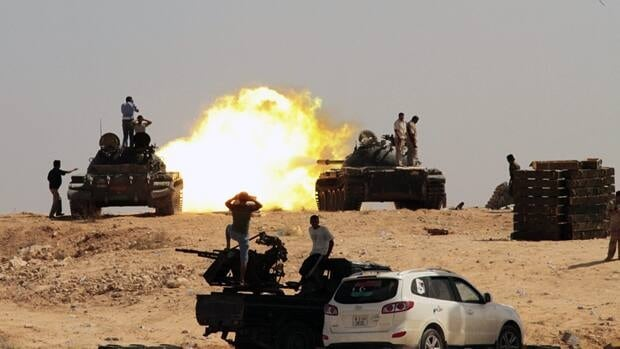 Revolutionary fighters fire from tanks towards Gadhafi troop positions in Sirte, Libya, on Sept. 26, 2011.