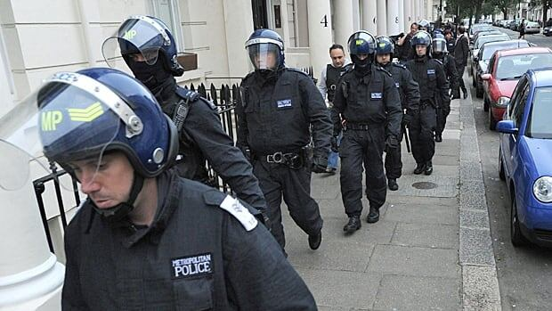 London police officers prepare to carry out a raid on a property on the Churchill Gardens estate in Pimlico.