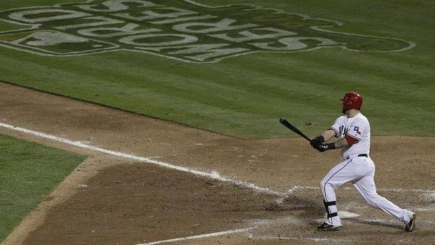 Texas Rangers' Mike Napoli hits a two-run double during the eighth inning of Game 5 of baseball's World Series against the St. Louis Cardinals, contributing to their win and putting the Rangers within one game of a World Series title.