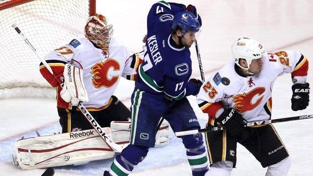 Vancouver Canucks centre Ryan Kesler, centre, tries to get a shot past Calgary Flames defenceman Scott Hannan, right, and goalie Leland Irving during the third period of Calgary's 3-1 win on Friday night.