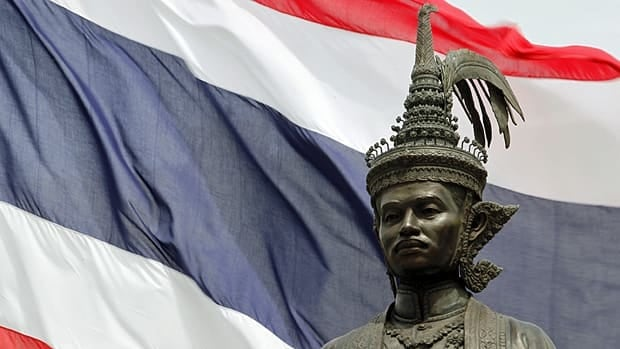 A Thai national flag waves in the wind behind a statue of King Rama VII in front of the parliament building in Bangkok ahead of a July 3 election.