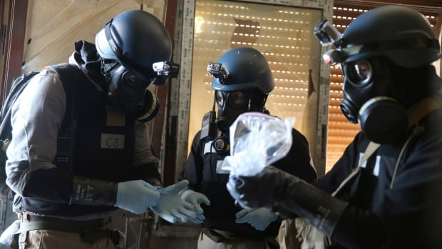Chemical weapons experts take samples from one of the sites of a chemical weapons attack in Damascus in August. A UN Security Council resolution the next month established a timeline for the dismantling and destruction of all of Syria's chemical weapons stockpiles and production facilities.