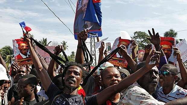 Supporters of former Haitian president Jean-Bertrand Aristide demonstrate in Port-au-Prince earlier this year. Aristide has been elected twice, thrown out twice and three times exiled. He was allowed back in the country two years ago.