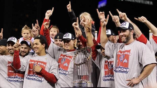 Jon Jay, left, Allen Craig, right, and Lance Berkman of the St. Louis Cardinals celebrate with the World Series trophy after defeating the Texas Rangers 6-2 on Friday night to capture the franchises' 11th crown.
