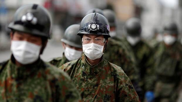 Members of Japan's Self-Defence Force walk in an area destroyed by the earthquake and tsunami in Ishinomaki, northern Japan on Sunday. Carlos Barria/Reuters